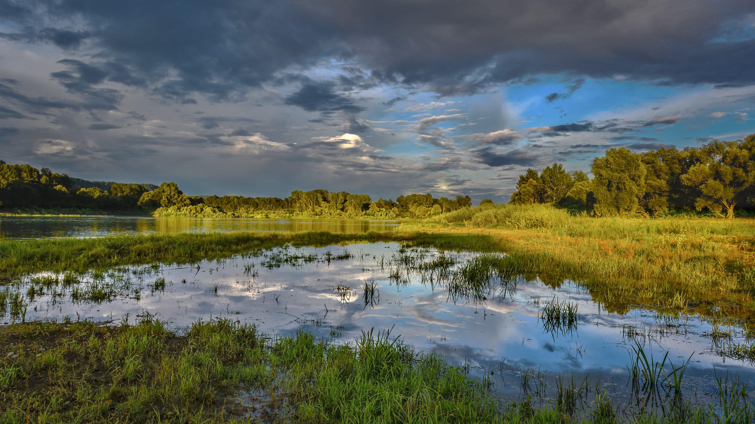 Cloudy sky over beautiful flood plain landscape. River landscape. Beautiful summer landscape with golden sunset. Flood plain of beautiful  river.
